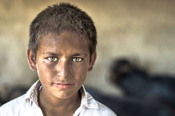 a blind young child is wearing black glasses - pakistano foto e immagini stock