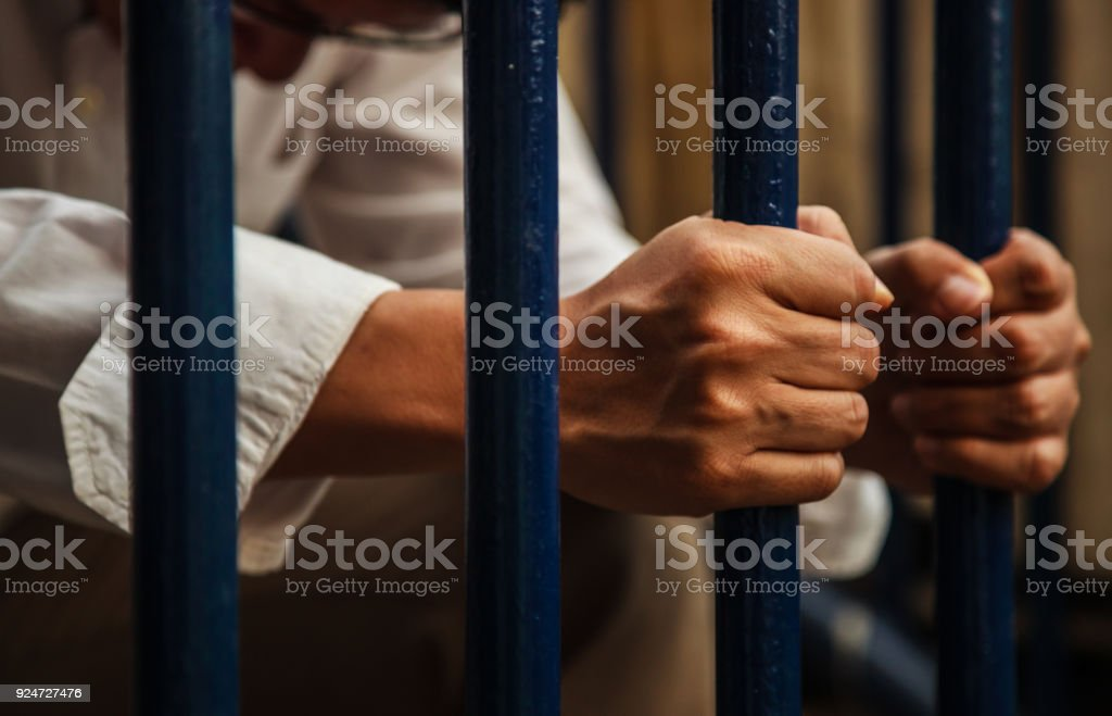a blue collar man wearing white shirt and brown slacks behind the iron fence, hand holding iron fence with a sense of hopelessness, sadness, solitude, sorrow, melancholy and isolation. stock photo