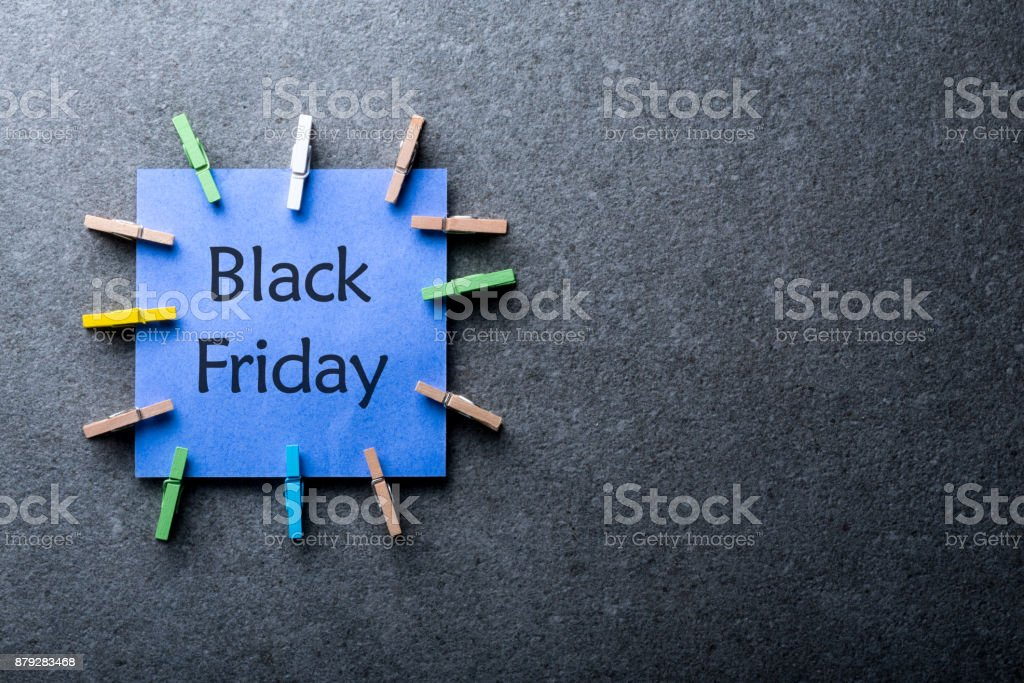 a blue paper label with the text black friday written in it against a dark gray background. Day with biggest Sale. Mockup stock photo