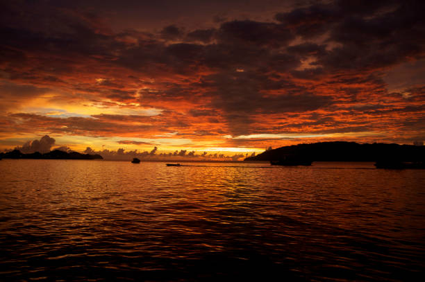 a boat crossing the sunset over the south china sea stock photo