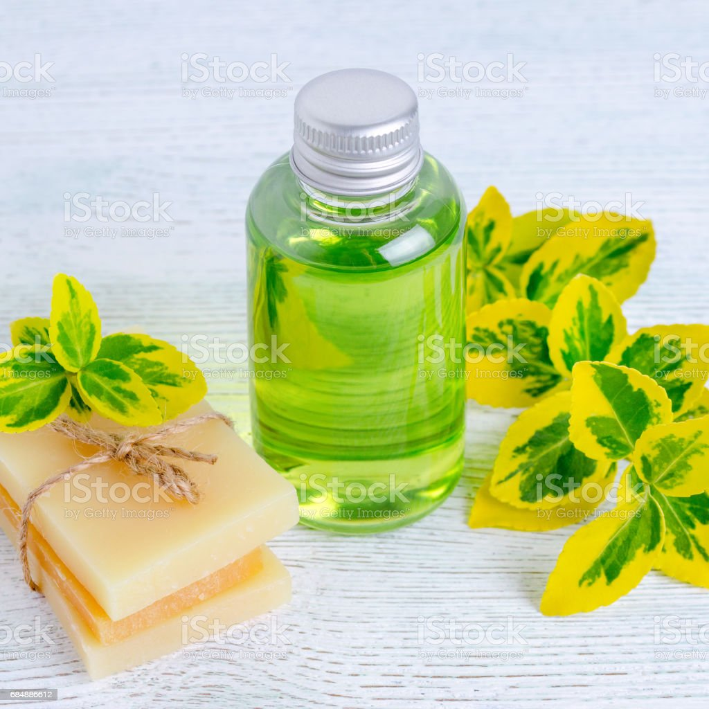 A Bottle Of Organic Liquid Soap And Homemade Herbal Soap Bar