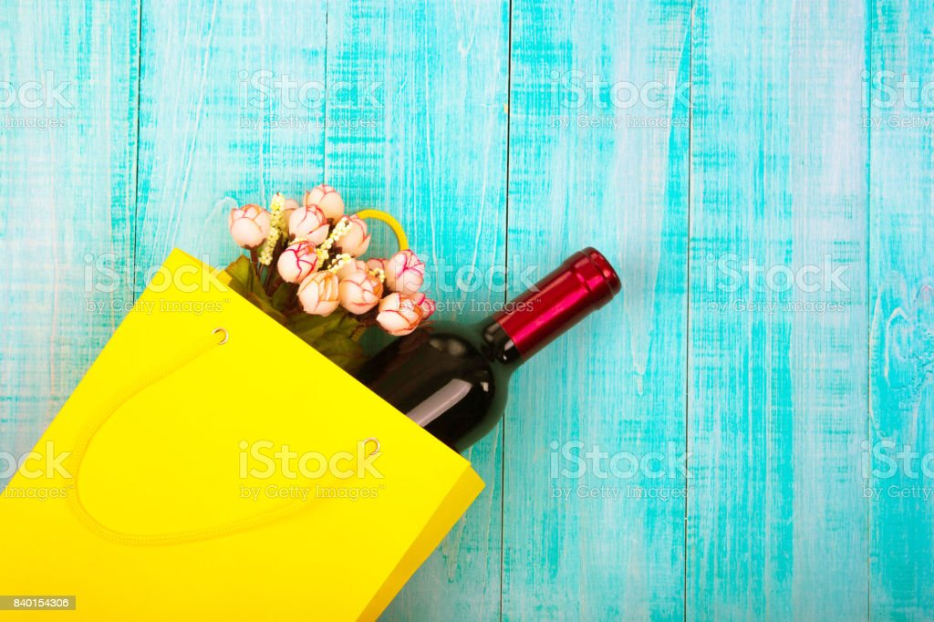a bottle of wine in a yellow package as a gift, next flowers, gifts,...