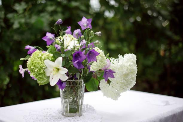 ein Strauß Gartenblumen steht in einer Vase – Foto