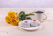 a bouquet of yellow roses, two heart-shaped cakes and a Cup of coffee on a wooden background