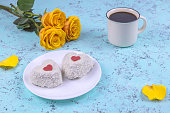 a bouquet of yellow roses, two heart-shaped cakes and a Cup of coffee on a blue background