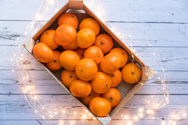 a box of ripe orange tangerines shot from above stock photo