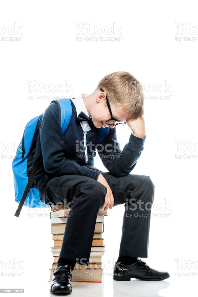 a boy in thought sits on a pile of books on a white background zbiór zdjęć royalty-free