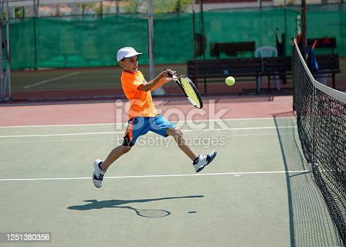 a boy is playing tennis on the hardcourt with forehand