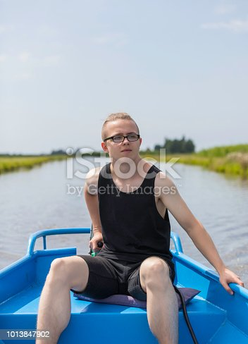 teenager boats through dutch polders in the rural landscape