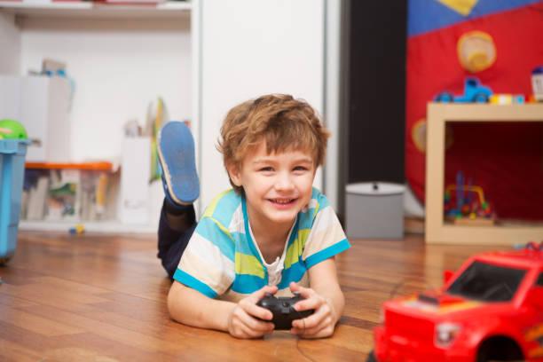 ラジオ制御車自宅で遊ぶ少年。 - リモート ストックフォトと画像