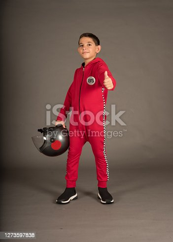 a boy wears red racing costume and he is holding helmet and singed ok
