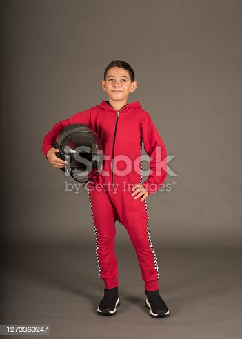 a boy wears red racing costume and he is holding helmet