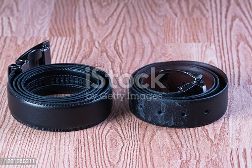 a comparison of brand new and old worn out leather belt