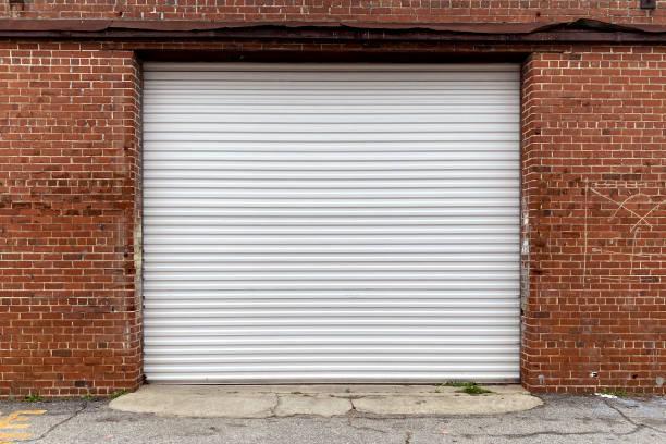 a brick wall warehouse with receiving door in an alley with metal garage doors stock photo