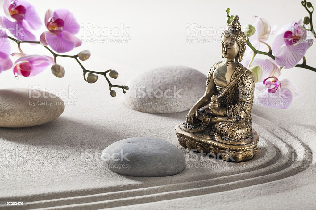 a bronze Buddha with sand and stones, for meditation and religion royalty-free stock photo