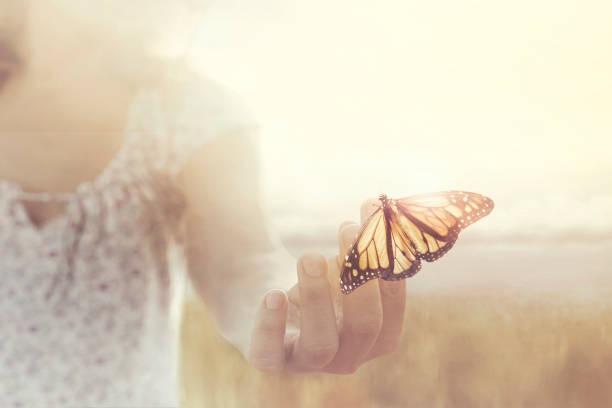 ein Schmetterling stützt sich auf eine Hand von einem Mädchen mitten in der Natur – Foto