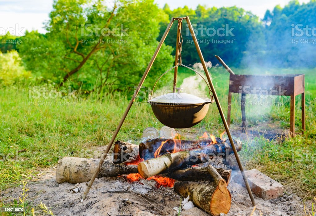 A Camp Steaky Sooty Food Bowl Hanging On Tripod Over Fire Royalty