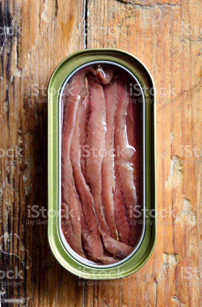 una lata de anchoas sobre una mesa - foto de stock