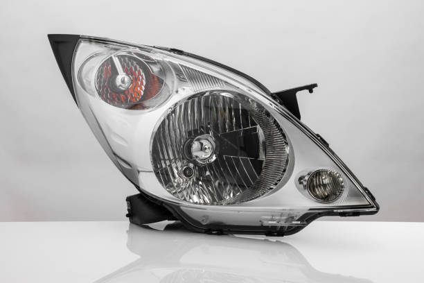 a car headlight on white background with reflection modern automotive headlight with reflection isolated on light background headlight stock pictures, royalty-free photos & images