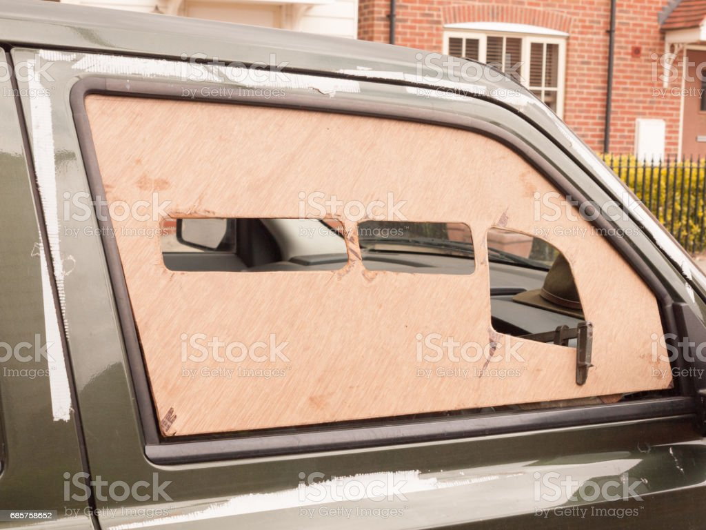 a car window boarded up with wood panel outside stock photo