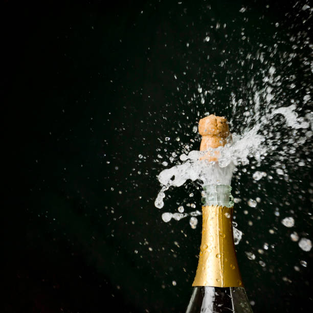 a champagne cork is popping out - champagne stock pictures, royalty-free photos & images