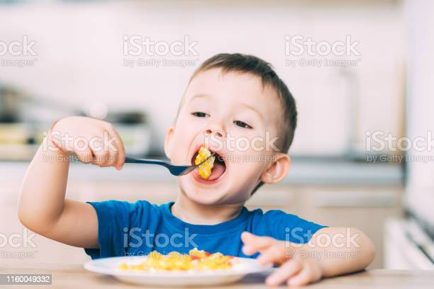 A child in a tshirt in the kitchen eating an omelet a fork picture id1160049332?b=1&k=6&m=1160049332&s=612x612&h=irs4z6omd 7cvmg2u5p efsxu7wbzby ri4k9vamj3k=