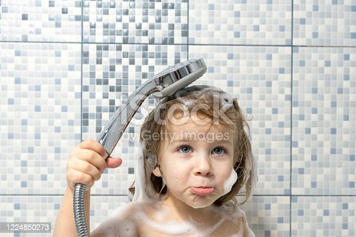 a child of 4 years old is covered with foam in the bathtub in his hand holding a shower, there is no water, the baby is upset. the child can not wash off the soap, water pipe breakage.