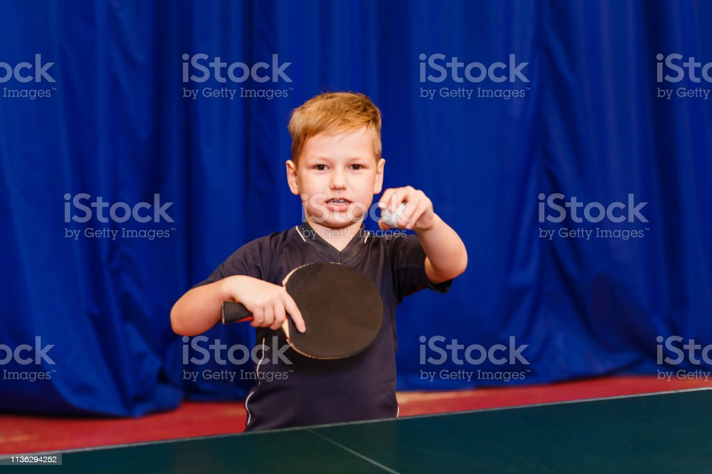 a child with a ball and a table tennis racket looks into the camera...