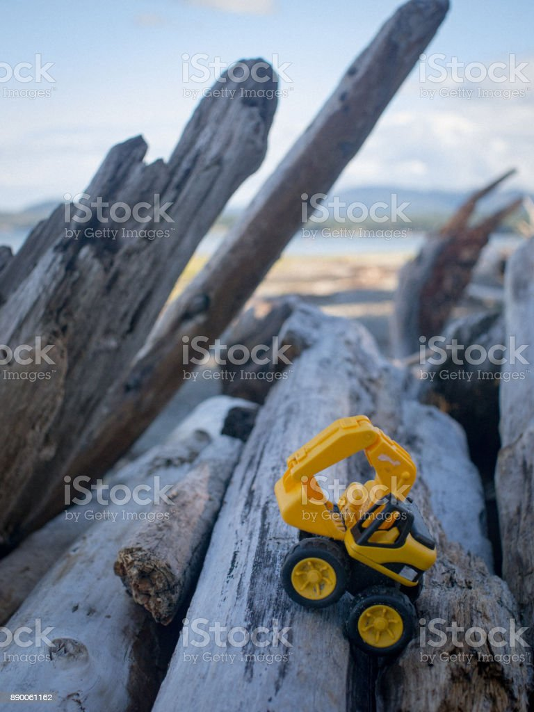 a child's toy excavator sitting on a pile of driftwood logs stock photo