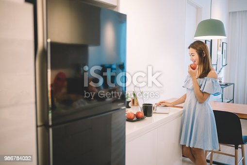 a chinese female looking at her laptop in the kitchen holding an apple