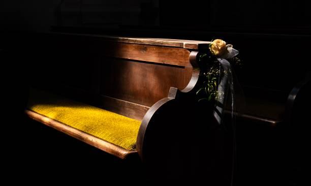eine Kirchenbank mit einer Rose für eine Hochzeit verziert – Foto