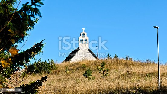 a Serbian Orthodox church with three small bells behind a hill