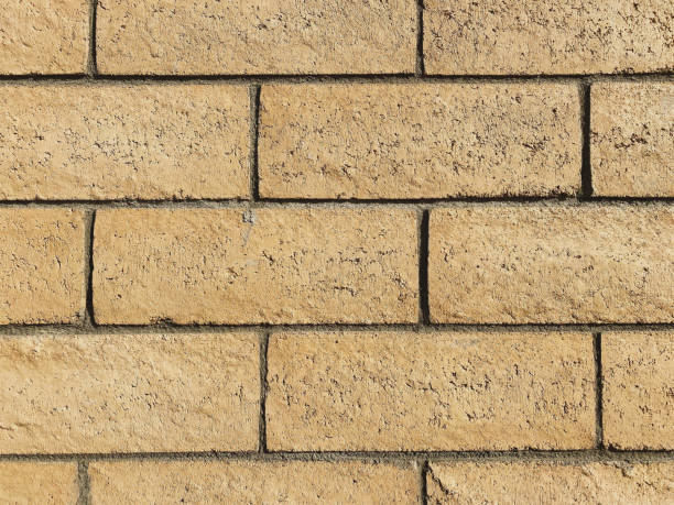 a close out view of tan brick block wall showing grout details, horizontal line design with bright natural sun light enhancing the rough details and textures stock photo