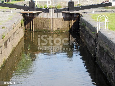 a close up of old closed wooden lock gates on the calder and hebble navigation canal in brighouse reflected in the water