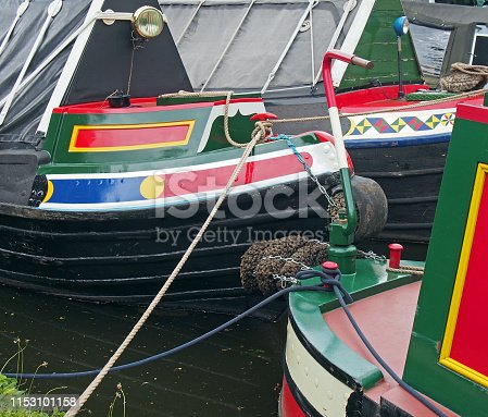 a close up of traditional british narrow boats painted in bright colors moored to a canal bank