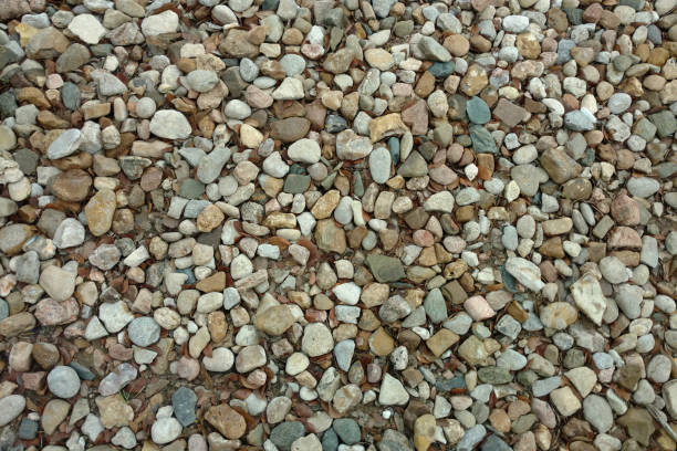 a close up view of a stone pebble rock gravel garden path backyard trail suitable for background backdrop also like a footpath walkway park featuring overhead detail textured surface pattern stock photo