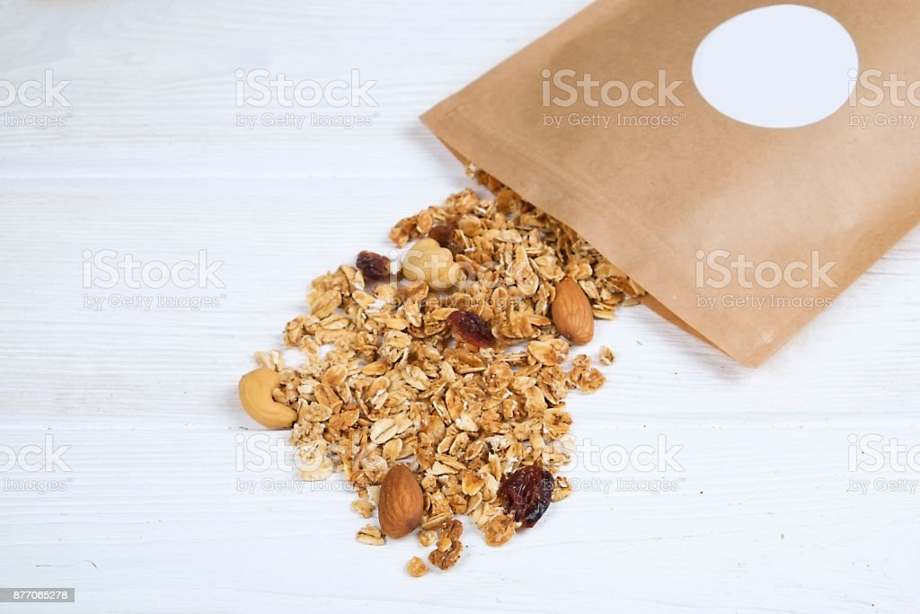a closup of sugar free granola cereal with nuts and dry fruits mix in the pack on white painted wood background, copy space stock photo