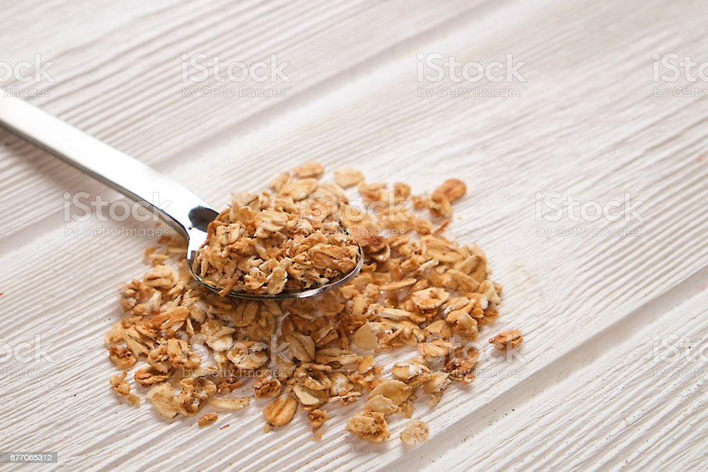 a closup of sugar free granola cereal with nuts and dry fruits mix on the spoon on gray painted wood background, copy space stock photo