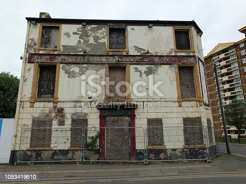the front of a collapsing fenced off derelict abandoned pub building in wakefield england awaiting demolition