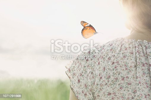 istock a colorful butterfly leans delicately on the shoulders of a girl 1071291568