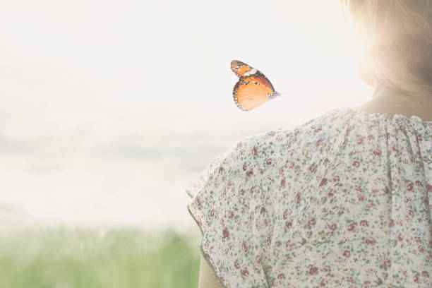 a colorful butterfly leans delicately on the shoulders of a girl a colorful butterfly leans delicately on the shoulders of a girl reincarnation stock pictures, royalty-free photos & images