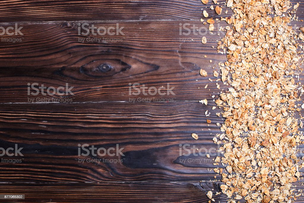 a contrasting close up of granola cereal with nuts mix on the dark brown table, copy space stock photo