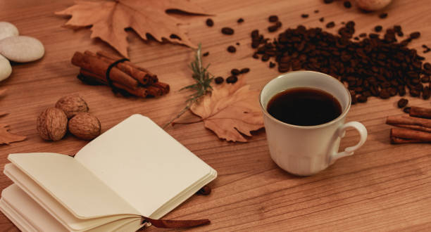 a cup of coffee and small notebook, winter aromatic decorations stock photo