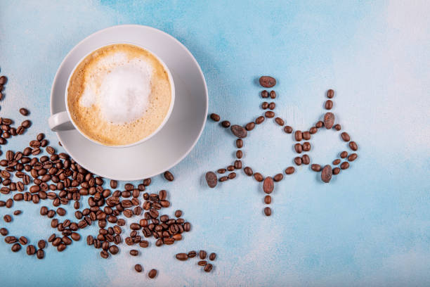a cup of coffee with caffeine molecule created by coffee beans. a cup of coffee with caffeine molecule created by coffee beans. Chemical formula of Caffeine with roasted coffee spill out of cup on blue wooden background. caffeine stock pictures, royalty-free photos & images