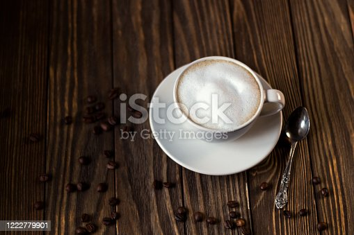 a Cup of coffee with milk and foam, coffee beans on a dark wooden background. selective focus.