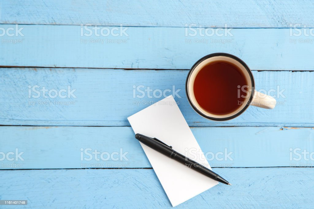 a Cup of drink and a paper notebook with a black pen on a blue wooden...