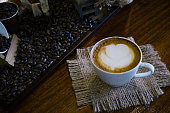 a cup of latte art on serves with decorated by coffee beens on the table make aromatic filling and waking up a day