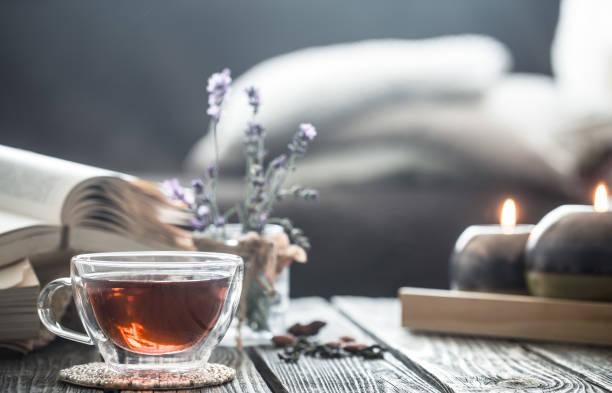 a cup of tea with a book in the interior - tea leaf stock photos and pictures
