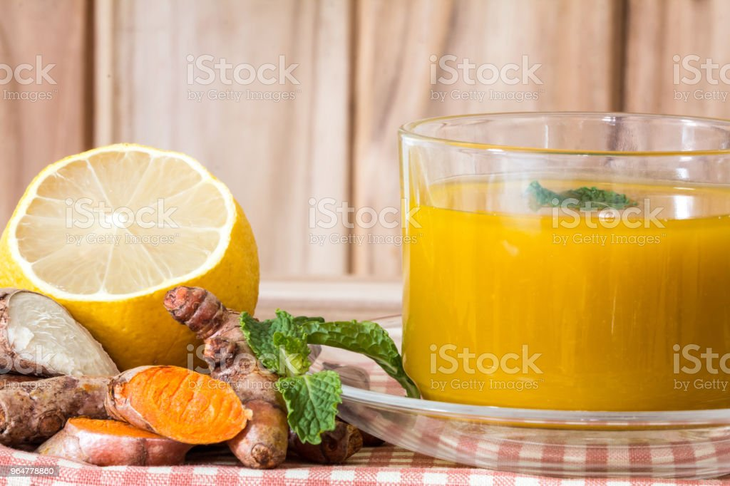 a cup of Turmeric Tea with lemon and ginger , Benefits for reduce Inflammation , Liver Detox and Cleanser healthy herb drink concept stock photo
