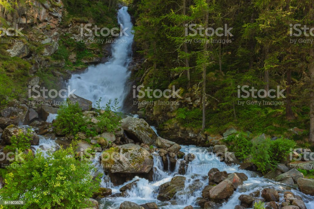 a deafening waterrfall falling from glaciers in the National Park of Great Paradise,in Piedmont,Italy. stock photo